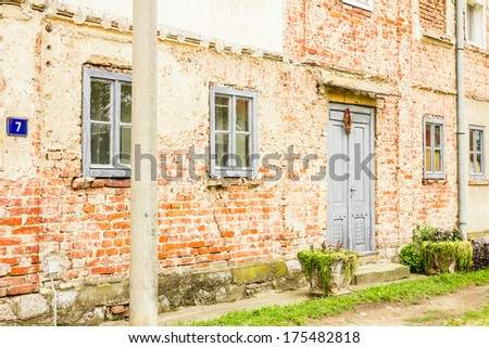 Old house brick wall with painted door and window - stock photo