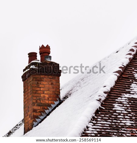 Old house clay brick chimney in winter covered with snow - stock photo