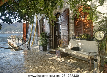 old house entrance with bench, clock and cat lying in Tivat, Montenegro - stock photo