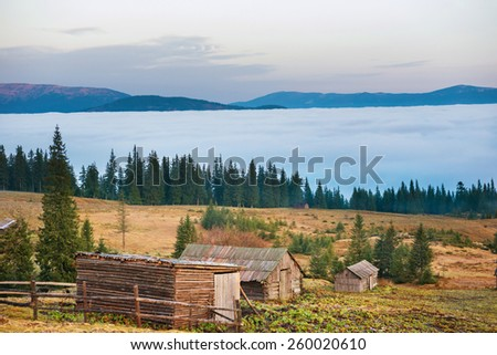 Old house in front of beautiful nature with clouds ocean, field of grass and mountains - stock photo