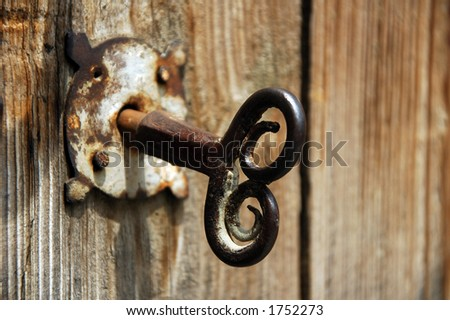 Old house key in wooden doors. - stock photo