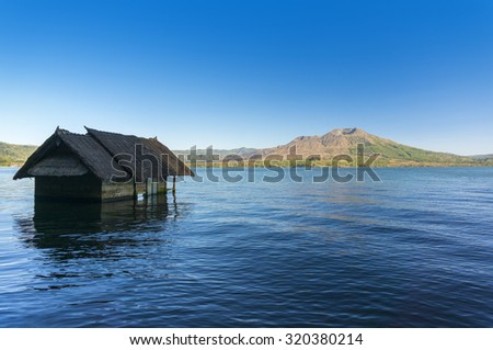 old house sunk in batur lake with batur mount background - stock photo
