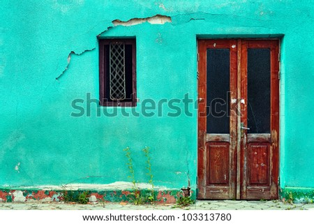 old house wall with wooden door and window - stock photo