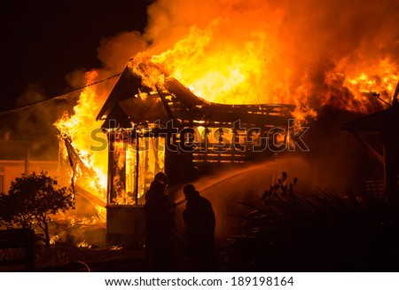 Old house well a blaze as fire men start to put is out. - stock photo
