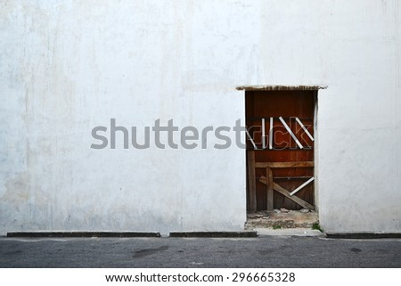 Old house white wall with wooden door. - stock photo