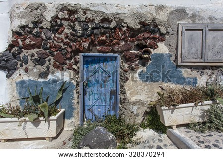 Old house with a blue door in Oia, Santorini - The Cyclades, Greece