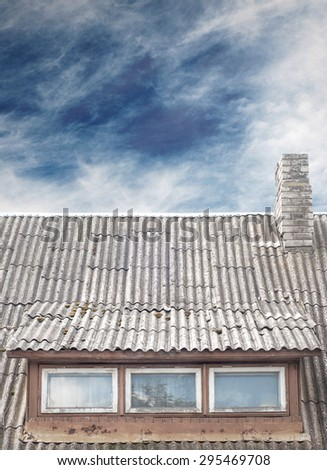 old house with a tiled roof and chimney, dramatic blue sky background - stock photo