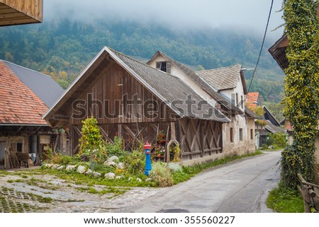 Old house with wooden extension and small green garden in front of it.