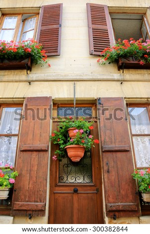 Old house with wooden shutters and door decorated with geranium flower pots. Ile-de-France, France. Retro aged photo. - stock photo