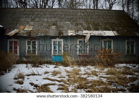 old house with wooden windows, in front of the house snow-covered grass