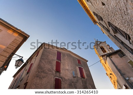 Old houses and Notre Dame de la Tour church tower in Sault, France against blue sky for copy space.