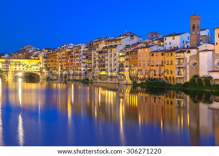 Old houses and tower on the embankment of the River Arno and Ponte Vecchio at night, Florence, Tuscany, Italy