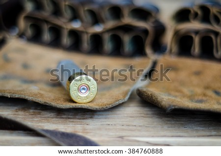Old hunting cartridge and leather bandoleer on a wooden table, selective focus - stock photo
