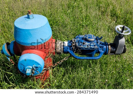 Old hydrant with an external valve - stock photo