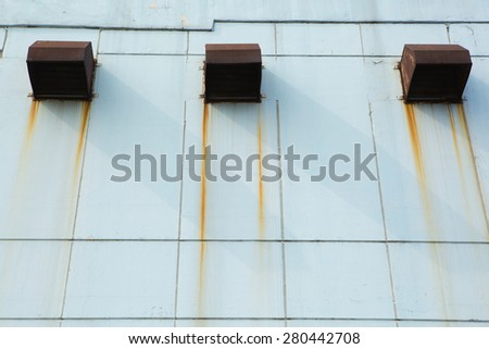 Old industrial air vent on blue wall - stock photo
