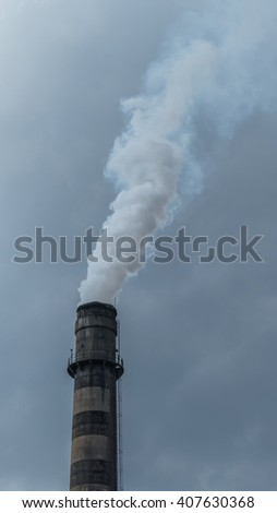 Old industrial chimney smoking in the sky - stock photo