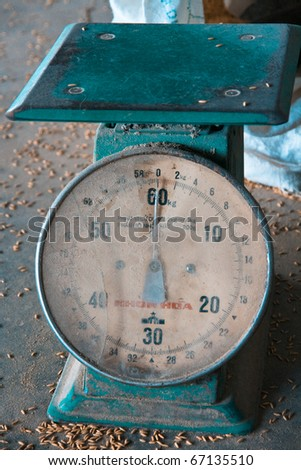 Old industrial rice scales on dustry warehouse floor - stock photo
