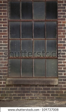 Old industrial windows with brick wall and concrete ground - stock photo