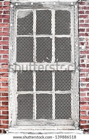 Old industrial windows with metal mesh protection in a brick wall - stock photo