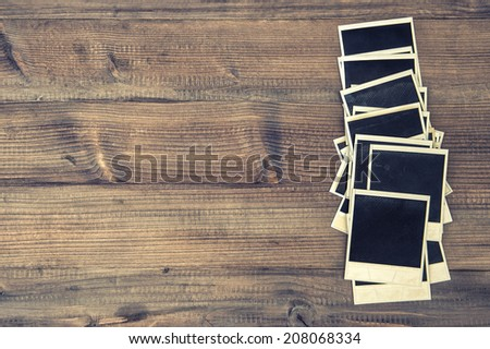 old instant photo frames on rustic wooden background. retro style toned picture