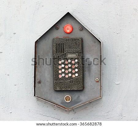 Old intercom on grey metal door - stock photo