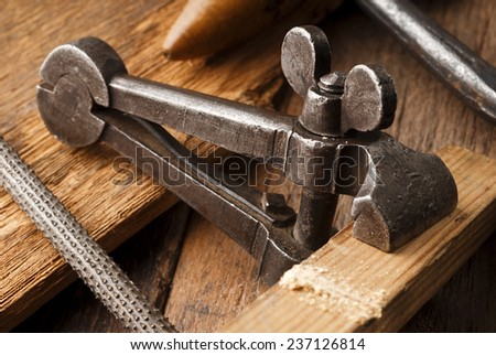 old iron clamp on aged wooden table - stock photo