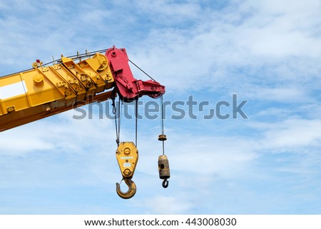 Old iron crane against blue sky with clouds. - stock photo