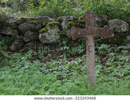 Old iron cross as tombstone besides a church ruin in Smaland, Sweden. - stock photo