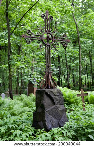Old iron cross on a tombstone, Smolensk Cemetery, St. Petersburg, Russia - stock photo