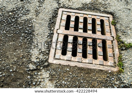 Old iron drain cover on asphalt road - stock photo