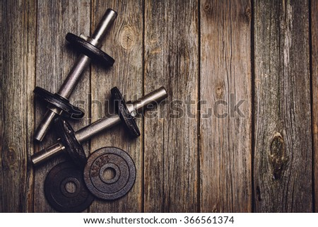 Old iron dumbbells or exercise weights with extra plates on an old wooden deck, floor or table. Image taken from above, top view. A lot of copy space around product. Horizontal photograph,