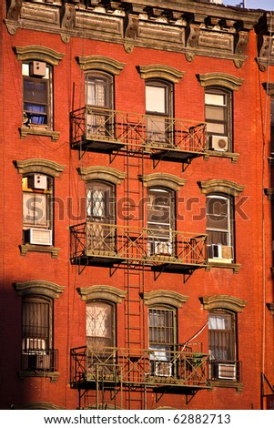 old iron fire escape rescue ladders at old houses in beautiful light