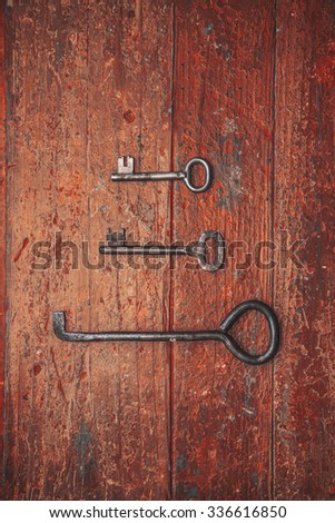 old iron keys on a wooden background top view