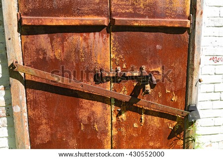 Old iron rusty door with  bolt on an ancient brick wall