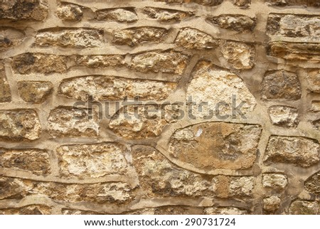 Old irregular golden stone wall, background. - stock photo