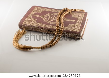 Old Islamic Book Holy Quran and beads on withe background,Note Text on the book is The holy quran Arabic Language.