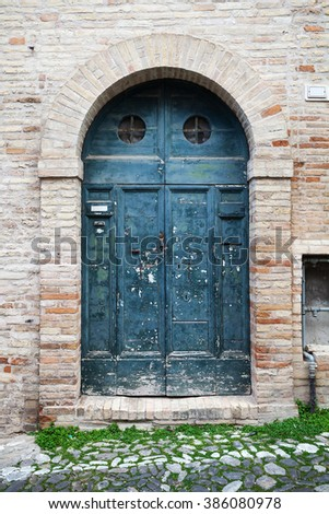 Old Italian architecture details. Blue wooden door with arch in old stone wall, background photo texture - stock photo