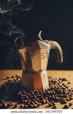 Old Italian coffee maker with coffee beans on canvas background