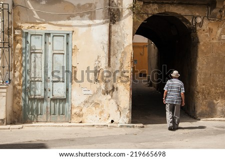 Old Italian man walking along ancient medieval lanes  in the city of Marsala, Sicily, Italy. - stock photo