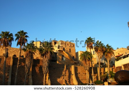 Old Jaffa at sunset colors, lots of palm trees and ancient buildings
