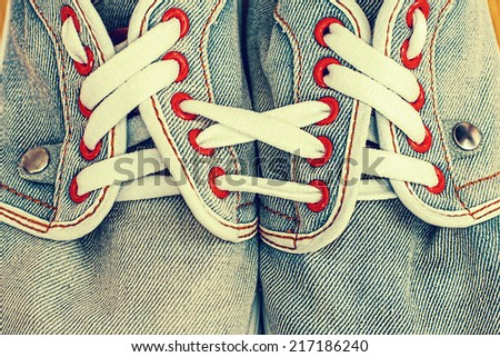 Old jeans sports shoes laced unusually - stock photo