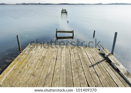 Old jetty wooden walkway pier on the lake - stock photo