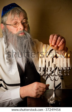 Old jewish man lighting candles of a hannukah menorah - stock photo