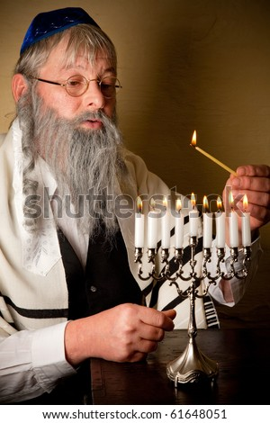 Old jewish man with beard lighting the candles of a menorah - stock photo