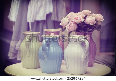 Old jugs on a table, toning in retro style - stock photo