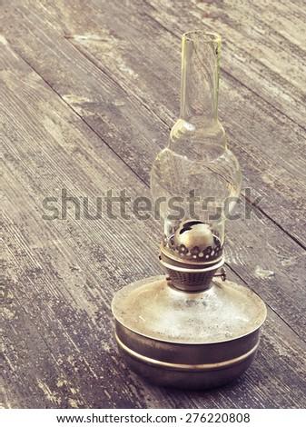 Old kerosene lamp on the wooden table. Vintage style toned photo. - stock photo