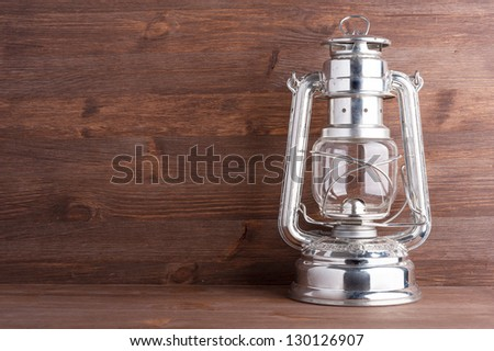 Old kerosene lantern on the dark wooden background