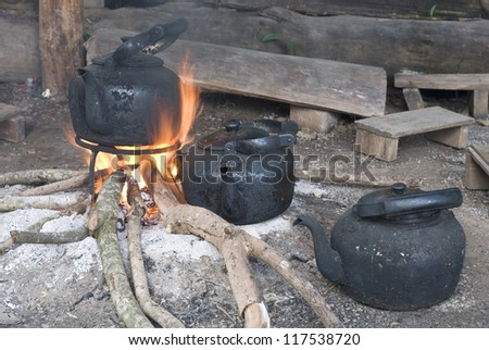Old kettle boiling water for mixing fresh Arabica coffee in countryside in Thailand - stock photo