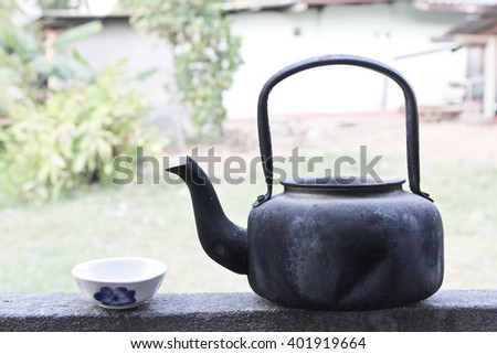 Old kettle for boiling hot water with ceramic cup ,selective focus