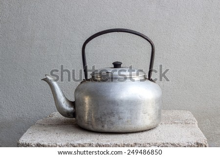 old kettle still life on brick block and concrete wall - stock photo